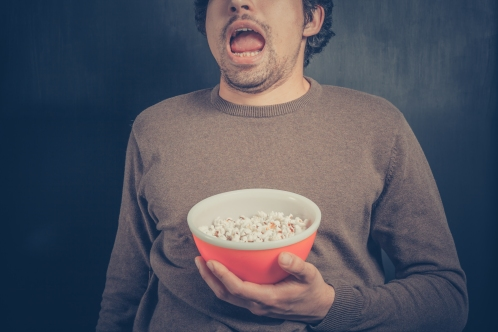 Shocked young man with popcorn